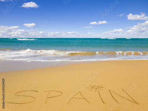 "The word ""Spain"" written on beach sand and seascape"