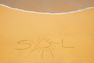 "The word ""Sol"" written on beach sand with wave approaching"