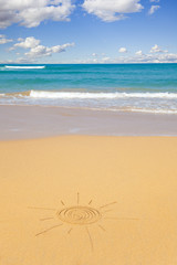 Sun shape written in sand with beach seascape