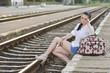 pretty young girl sitting on platform, waiting the train