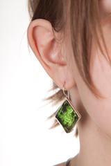 Amber earring on female ear.