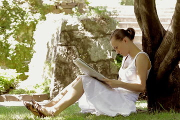 Woman sitting in the garden and reading newspaper, dolly shot