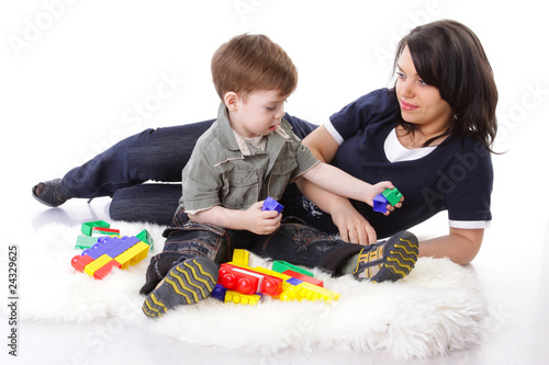 Devoted mother playing with colored blocks with her curious son