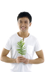 Close up asian man holding a fern leaf