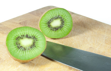 cut kiwi fruit on chopping board isolated on white
