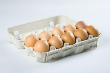 Ten fresh brown eggs on a grey background