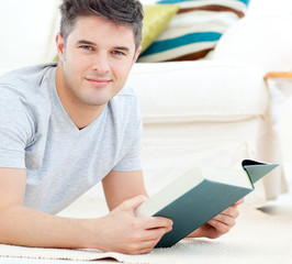 Happy young man looking at the camera holding a book