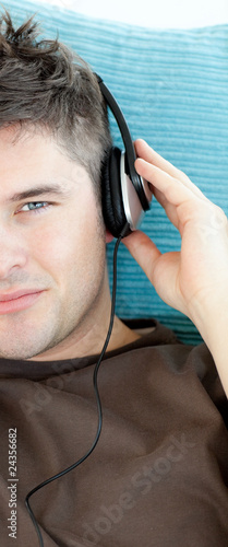 Charming young man listening to music with headphones