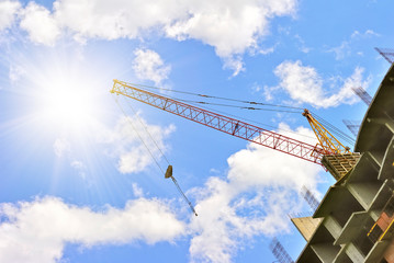 Building with elevating crane and sky with sun