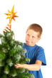 Young boy grimacing while decorating Christmas tree