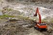 Excavator standing in sandpit with risen bucket