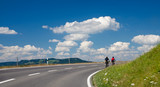 two bicyclists on road with a perfect sky poster