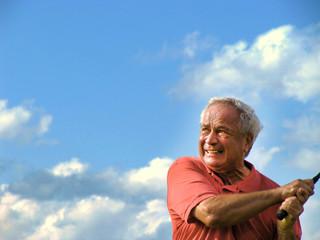 Seniorengolfer beim Abschlag gegen Himmel