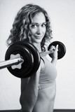 A young woman is engaged in weightlifting poster