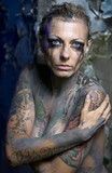 Naked tattooed woman with smeared makeup