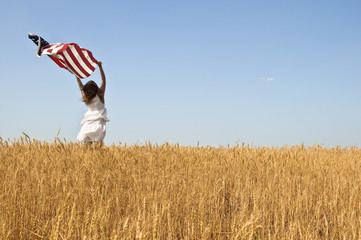 Beautiful young girl holding an American flag in the wind