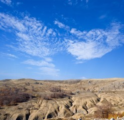 cracked stony desert under a blue clouds