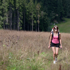 young woman hiking outdoors (going uphill)