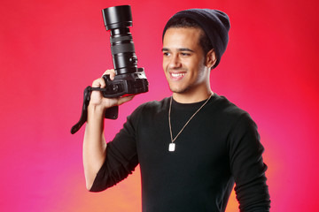 Young photographer on red background