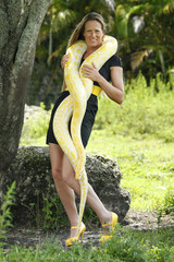 Young woman plays with an albino burmese python