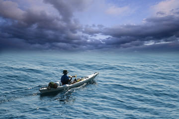 Young man in sea kayak under dramatic skies