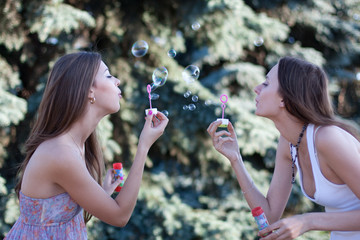 Two young women make soap bubbles