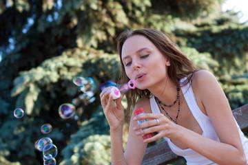 young woman makes soap bubbles