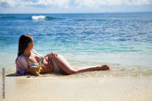 Young dark haired model lying in water on the beach