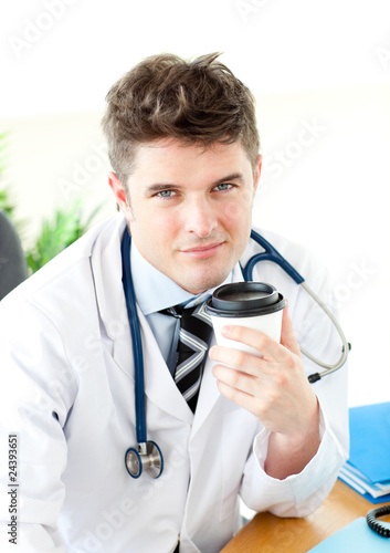 Attractive doctor drinking a hot coffee in an office