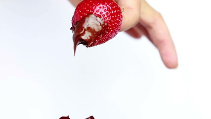 The process of dipping strawberries in chocolate sauce.