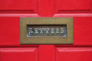brass letterbox and red door