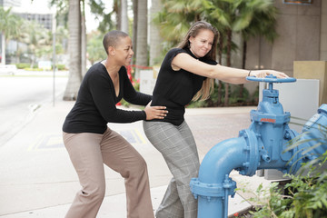 Women struggling to turn off the valve
