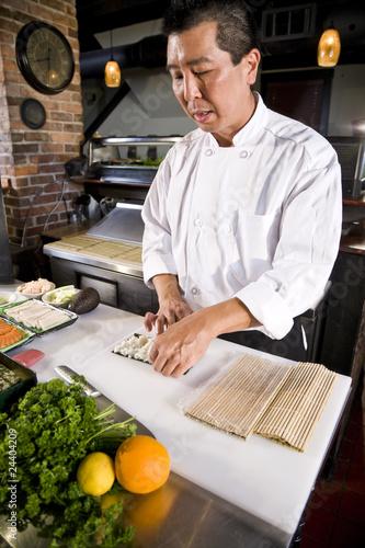 Japoński szef kuchni w restauraci robi suszi rolce