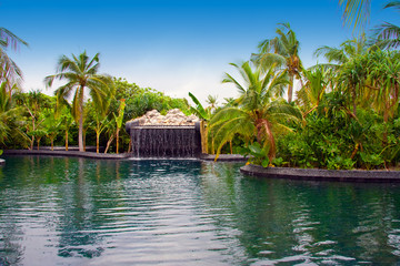 Maldives. .Pool with small fall in tropical garden.
