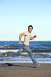 Handsome young man running barefoot on beach in casual wear