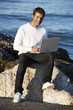 Young man using laptop at beach