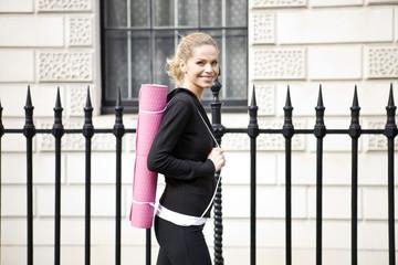 A mid adult woman carrying a yoga mat, walking