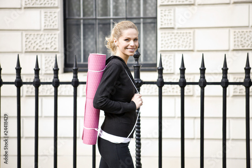 A mid adult woman carrying a yoga mat, walking