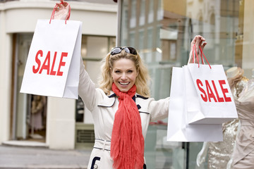 A mid adult woman holding up some sale bags, smiling