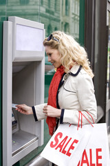 A mid adult woman using a cash machine, carrying sale bags