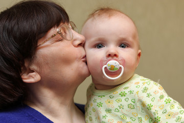 Grandmother kisses baby