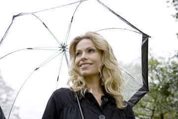 A mid adult woman holding an umbrella