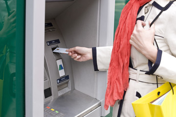 A woman using a cash machine, close-up