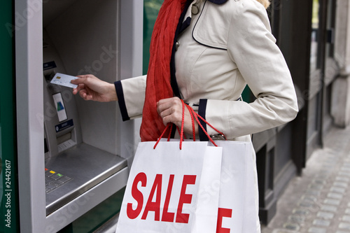 A woman using a cash machine, carrying sale bags, close-up