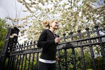 A mid adult woman jogging, wearing headphones