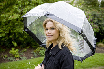A mid adult woman walking along, holding an umbrella