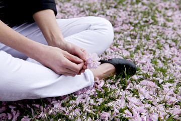A woman sitting in the grass, holding a flower