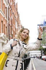 A mid adult woman hailing a taxi
