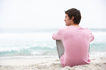 Young Man On Holiday Sitting On Winter Beach
