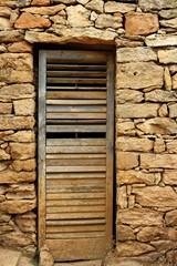 aged wood door on masonry stone wall